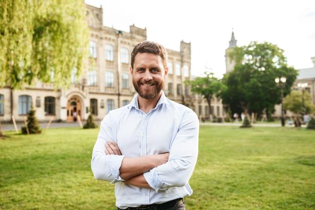 Uomo adulto sorridente in camicia bianca che cammina nel parco verde mentre in piedi con le braccia conserte sul vecchio edificio