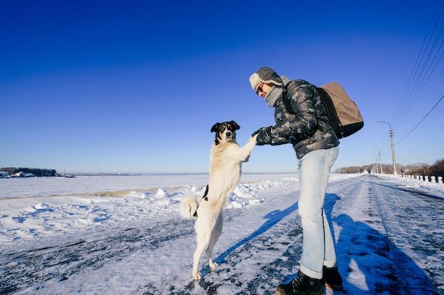 Uomo adulto alla moda in posa con cane amichevole nel campo di neve