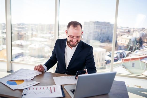 Uomo d'affari adulto di successo, insegnante, mentore sta lavorando a un nuovo progetto. si siede al tavolo vicino alla grande finestra. funziona su un laptop