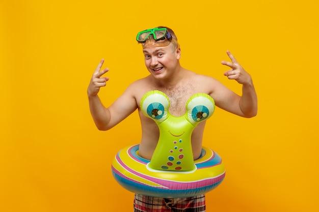 Uomo adulto in topless in forma di anello di gomma di lumaca e maschera subacquea in posa