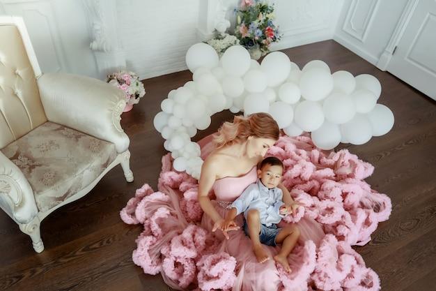 Una donna adulta una bella madre in un vestito rosa soffice tiene in braccio suo figlio dall'aspetto asiatico