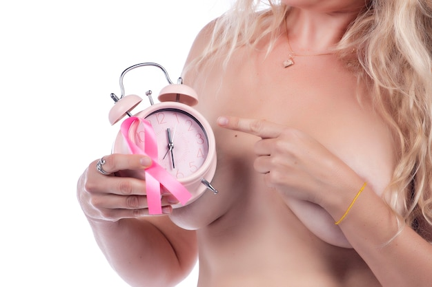 Donna adulta che copre i seni con le mani che tengono il nastro rosa di consapevolezza del cancro al seno e un orologio, sopra un bianco.
