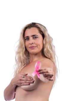 Donna adulta che copre i seni con le mani che tengono il nastro rosa di consapevolezza del cancro al seno, sopra un bianco.