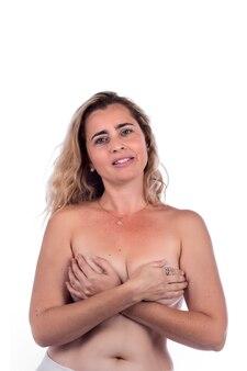 Donna adulta che copre i seni con le mani sopra un bianco.