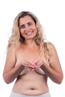Donna adulta che copre i seni con le mani con il nastro rosa di consapevolezza del cancro al seno, su un bianco.
