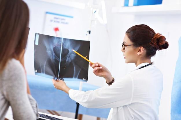 Donna adulta che discute i risultati dei raggi x durante la visita presso l'ufficio del medico femminile
