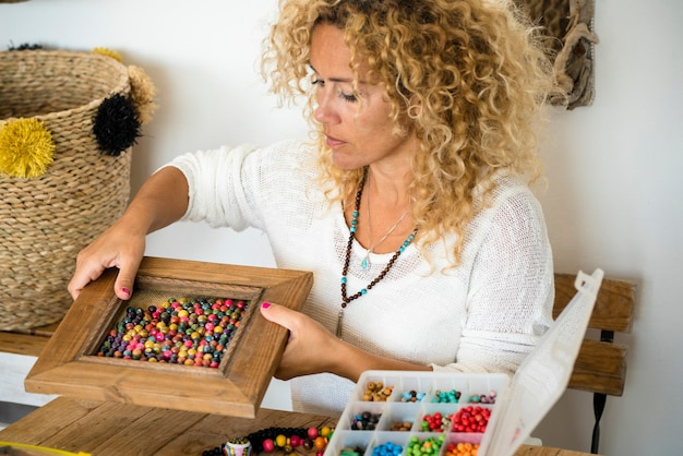 Donna adulta che fa gioielli di creazioni fatte a mano a casa con perline colorate e corde