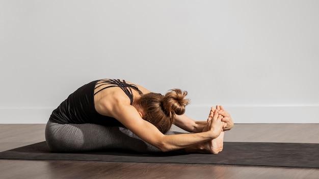 Donna adulta che fa yoga a casa