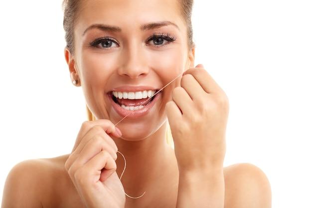 Donna adulta che usa il filo interdentale sui denti isolati su bianco