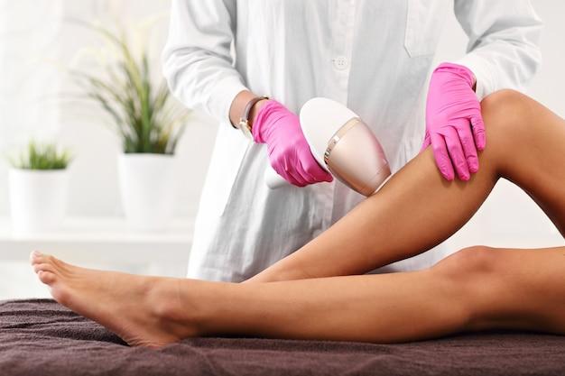 Donna adulta che ha la depilazione laser nel salone di bellezza professionale