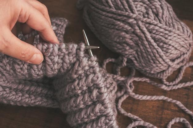 Una donna adulta tiene in mano ferri da maglia di colore grigio pallido