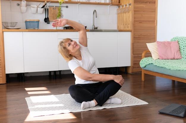 Una donna adulta è impegnata nel fitness a casa