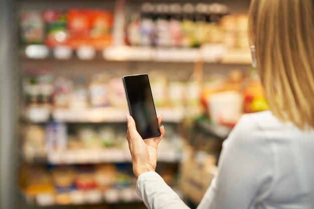 Donna adulta in maschera medica che utilizza smartphone e fa la spesa