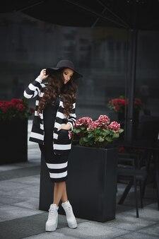 Donna adulta in un cappello nero alla moda e scarpe bianche alla moda in posa sulla strada della città europea