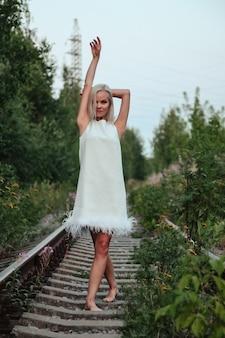 Donna adulta sulla natura che cammina nella foresta estiva sulla ferrovia del crepuscolo. signora sognatrice in abito a piedi la sera sulla ferrovia. emozione positiva femminile sui binari all'alba