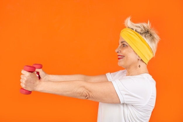 Pensionato donna adulta va a fare sport con i manubri