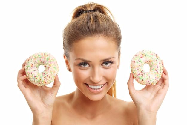 Donna adulta in posa con ciambelle su sfondo bianco
