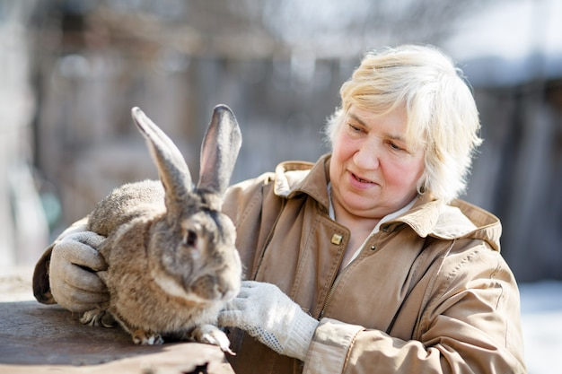 Donna adulta e allevamento di conigli. concentrati sulla donna