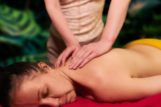 La donna adulta riceve un massaggio alla schiena da un massaggiatore privato