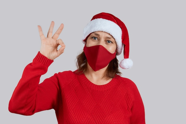 Una donna adulta con una maschera protettiva rossa, con un cappello da babbo natale su uno sfondo grigio mostra il gesto ok. natale, capodanno in quarantena.