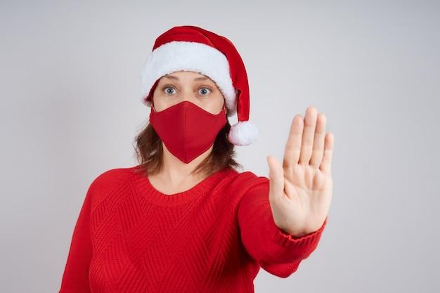 Una donna adulta con una maschera protettiva rossa, un cappello da babbo natale su uno sfondo grigio, mostra un gesto di arresto. natale, capodanno in quarantena.