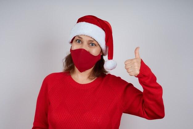 Una donna adulta con una maschera protettiva rossa, con un cappello da babbo natale su uno sfondo grigio, mostra un gesto di pollice in alto. natale, capodanno in quarantena.