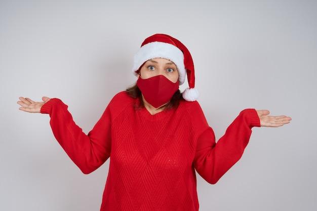 Una donna adulta con una maschera protettiva rossa, un cappello da babbo natale su uno sfondo grigio, allargò le braccia per la sorpresa. natale, capodanno in quarantena.