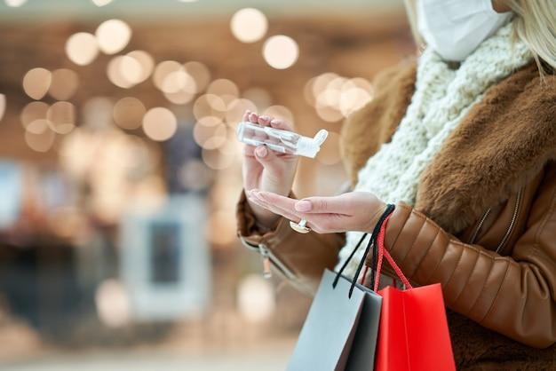 Donna adulta che fa shopping nel centro commerciale indossando una maschera e usando disinfettante per le mani, concetto di coronavirus