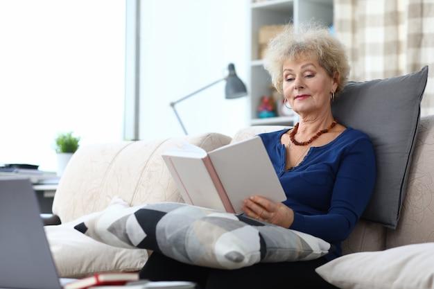 La donna adulta si siede sul divano a casa e legge il libro.