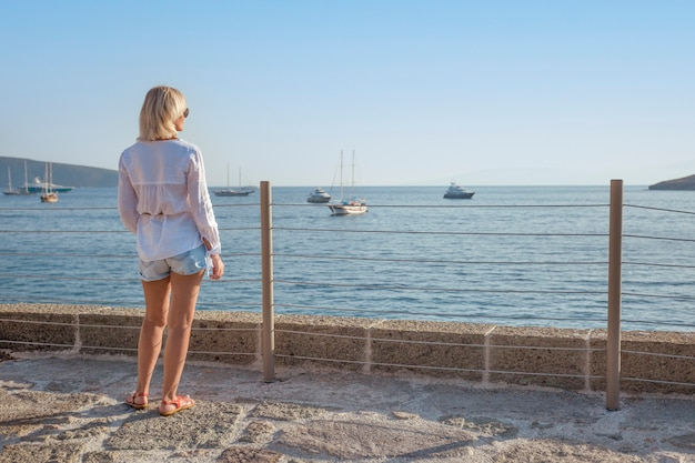 Viaggiatore della donna adulta che sta e che gode della splendida vista del porto di bodrum