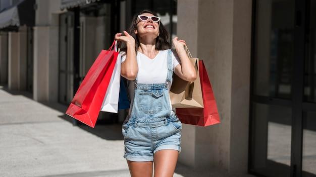 Donna adulta che cammina con i sacchetti della spesa
