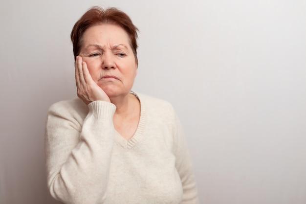 Donna adulta su bianco in un maglione leggero.
