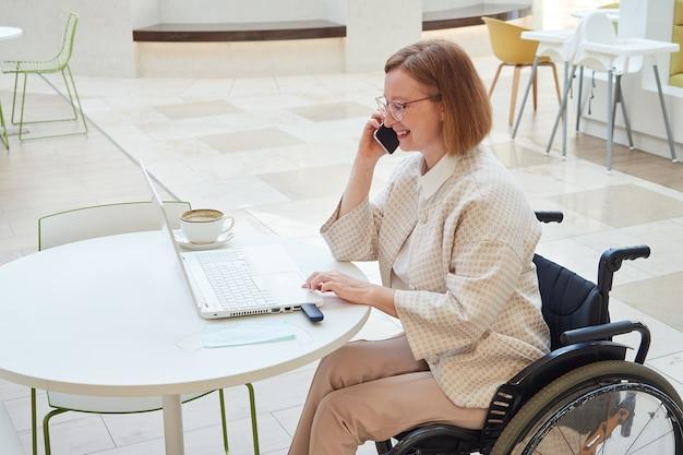 Donna adulta con gli occhiali in una sedia a rotelle che lavora al computer portatile
