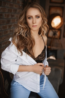 Donna adulta con trucco perfetto e capelli biondi in una camicia bianca sbottonata e reggiseno nero in posa all'interno