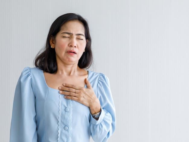 Donna adulta con infarto improvviso e tenere il petto con dolore al viso. concetto di assistenza sanitaria di emergenza e affetto da insufficienza congestizia o rianimazione cardiopolmonare, problema cardiaco.