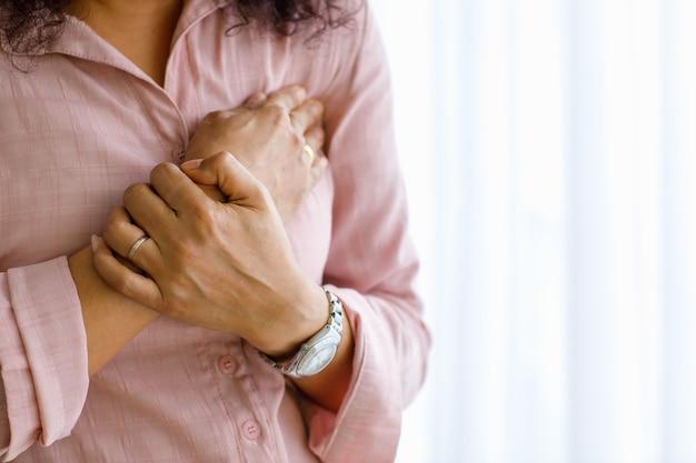 Donna adulta con infarto improvviso e usa il petto della stretta della mano con il viso distorto. concetto di assistenza sanitaria di emergenza e affetto da insufficienza congestizia o rianimazione cardiopolmonare, problema cardiaco.