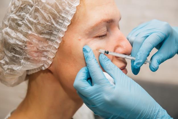 Donna adulta con rughe intorno agli occhi in iniezioni di ringiovanimento del processo di filler di acido ialuronico, primo piano. il cosmetologo inietta la tossina botulinica per levigare la pelle del viso femminile.