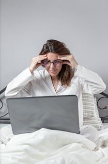 Donna adulta che lavora a casa in pigiama