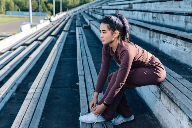 Una giovane ragazza adulta di aspetto asiatico in una tuta viola si siede su una panca di legno, distoglie lo sguardo e lega un laccio.