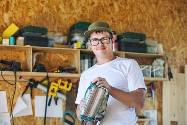 Giovane adulto che lavora in una falegnameria che lavora con gli strumenti sul prodotto
