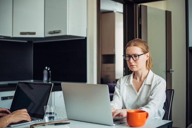 Giovane donna adulta in occhiali e camicia bianca che lavora con il computer portatile in un ufficio a casa. mani che digitano sulla tastiera, bevande. libero professionista, coworking, lavoro a distanza, lavoro autonomo, isolamento.
