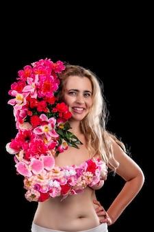 Giovane donna adulta con il braccio coperto di fiori che simboleggiano il concetto della madre terra sopra un nero.