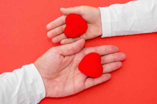 Mani di adulti e bambini che tengono cuore rosso, amore per la salute, dare, speranza e concetto di famiglia, giornata mondiale del cuore, giornata mondiale della salute