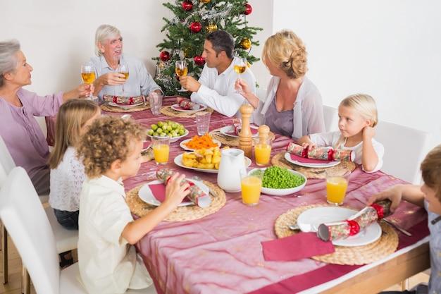 Adulti che alzano gli occhiali alla cena di natale