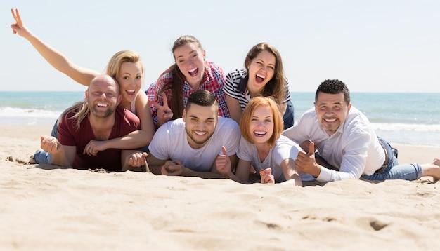 Adulti che si rilassano in spiaggia sabbiosa