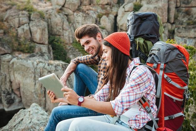 Coppia avventurosa con tavoletta vicino al canyon, seduto alla roccia