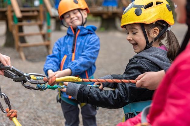 Parco avventura arrampicata ad alta fune - bambini in corso in casco da montagna e equipaggiamento di sicurezza.