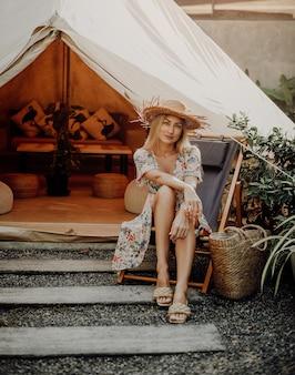 Avventura in thailandia. viaggiatrice allegra e ottimista durante il suo viaggio in thailandia. la giovane donna posa sulla sedia sullo sfondo del suo accampamento.