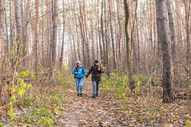 Concetto di avventura, viaggi, turismo, escursione e persone - coppia sorridente che cammina con gli zaini sulla superficie naturale autunnale