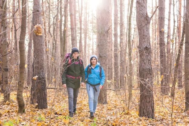 Avventura, viaggi, turismo, escursione e concetto di persone - coppia sorridente che cammina con zaini su sfondo naturale.